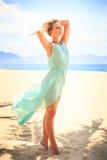 天蓝色的白肤金发的女孩调查在海滩的照相机 图库摄影