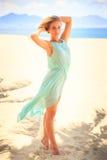 天蓝色的白肤金发的女孩调查在海滩的照相机 免版税库存照片