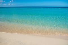 天蓝色的绿松石风平浪静、明白蓝天、沙滩和平的天际 免版税库存照片