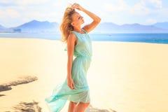 天蓝色神色的白肤金发的女孩批转风在海滩的震动头发 免版税库存图片