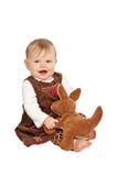 天鹅绒礼服的愉快的婴孩使用与被充塞的玩具 免版税库存照片