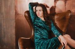天鹅绒礼服的美女,坐在皮革棕色ch 免版税库存照片