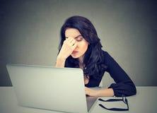 太工作 坐在膝上型计算机前面的书桌的疲乏的困妇女 免版税库存图片