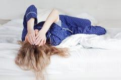 太懒惰以至于不能离开床,用手盖她的面孔的妇女 免版税库存图片