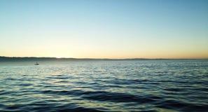 太阳上升在离海岸的附近 免版税库存照片