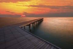 太阳上升天空和老木桥梁码头 免版税库存照片