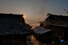 太阳上升的behingtraditional中国少数房子 免版税库存照片