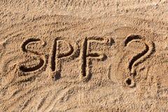 太阳保护因素概念 在与问号的海滩写的SPF词 免版税图库摄影