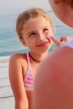 太阳保护母亲涂油她的女儿面孔防护奶油 免版税图库摄影