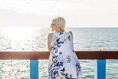 太阳保护玻璃的美丽的妇女在桥梁站立并且敬佩海的秀丽 库存照片