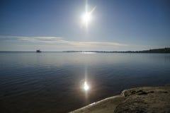 太阳光和一深蓝色湖自然backgound贴墙纸 库存图片