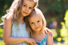太阳光的两个拥抱的逗人喜爱的小女孩 免版税库存照片