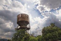 太阳光芒发光的老储水箱 图库摄影