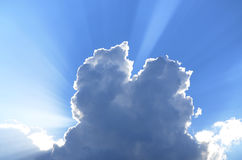太阳光芒看后边在蓝天的cumunus云彩 免版税库存照片