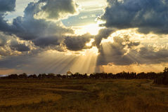 太阳光芒通过在公墓背景的天空 免版税库存照片