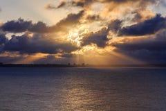 太阳光芒通过在海的云彩 免版税库存照片