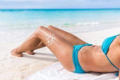 太阳关心遮光剂比基尼泳装棕褐色妇女海滩晒黑 免版税库存照片