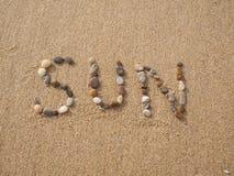 太阳写与石头和壳 免版税图库摄影