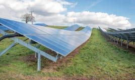 太阳农场 太阳电池板,绿色领域蓝天 免版税库存照片