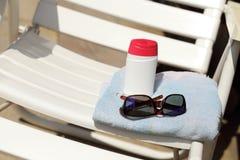 太阳化妆水和玻璃在毛巾 库存照片