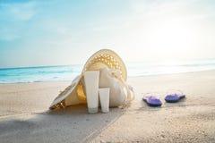 太阳化妆水,有袋子的帽子在热带海滩 免版税库存图片