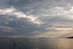太阳发出光线出来通过在一个海岛的云彩湖的, 库存图片