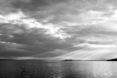 太阳发出光线出来通过在一个海岛的云彩湖的, 免版税库存图片