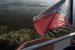 太阳发出光线发光与在风的一面旗子在小船 免版税库存照片