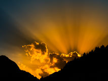 太阳发出光线发光从云彩的后面 与mountail剪影的日落时间 免版税库存照片
