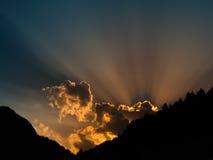 太阳发出光线发光从云彩的后面 与mountail剪影的日落时间 免版税图库摄影