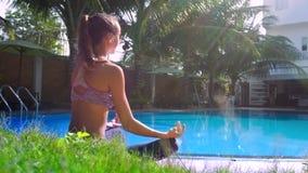 太阳发出光线放松在姿势莲花的轻的女孩由水池侧视图 股票录像