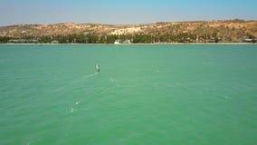 太阳发出光线浅褐色的小山和风帆冲浪者风帆沿岸航行 股票视频