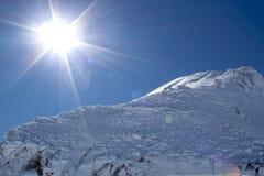 太阳和一个峰顶在山的上流 库存图片