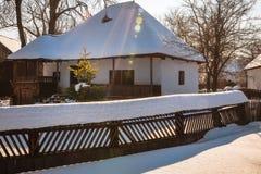 太阳在一个老传统房子前面的一棵`圣诞节`树发出光线 免版税库存图片