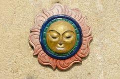 太阳在亚洲房子墙壁上的标志面具 免版税库存照片