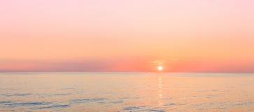 太阳在天际设置在海或海洋的日落日出 图库摄影