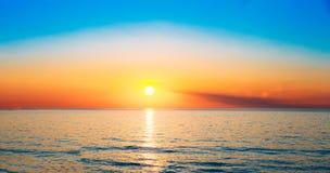 太阳在天际设置在海或海洋的日落日出 T 库存照片