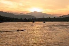 太阳在山后设置,点燃一个渔船的最后光芒,在一个热带海湾停住 泰国 免版税库存图片