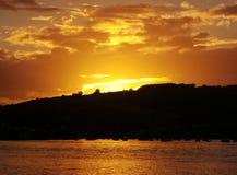 太阳在有森林的海设置了 免版税库存照片