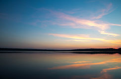 太阳在湖设置了在森林里 免版税图库摄影
