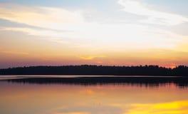 太阳在湖设置了在森林里 免版税库存照片