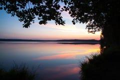 太阳在湖设置了在森林里 免版税库存图片