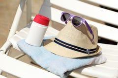 太阳帽子和玻璃在毛巾 库存照片