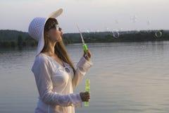太阳帽子的白人妇女做打击泡影 免版税库存图片