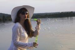 太阳帽子的白人妇女做打击泡影 库存照片
