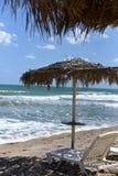 太阳床和一把伞在一个美丽的离开的海滩接近海波浪 免版税图库摄影