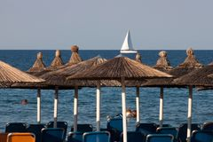 太阳床和伞在希腊海岛上有一艘帆船的在backround 免版税图库摄影