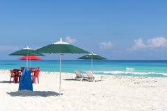 太阳懒人、椅子、桌和伞在一个热带海滩 库存图片