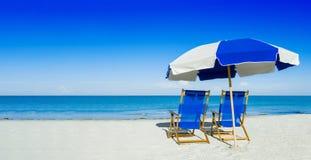 太阳懒人和一把沙滩伞在银色沙子,假期浓缩 免版税库存照片