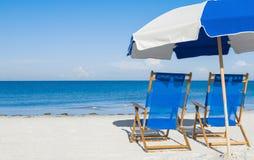 太阳懒人和一把沙滩伞在银色沙子 免版税库存照片
